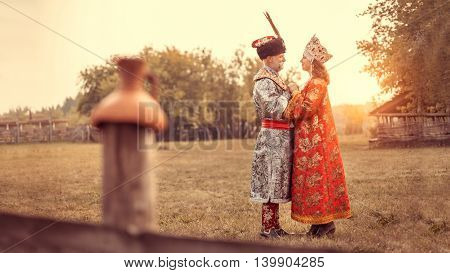 King and Queen dressed in medieval clothes on the rural summer background.