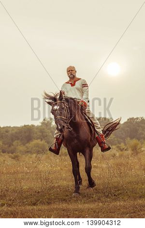 Man in ethnic clothing is riding a horse on the summer fields background.