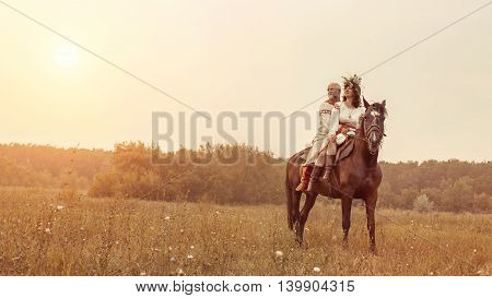 Mature Man And Woman In Ethnic Clothes Are Riding A Horse On The Rural Summer Background.
