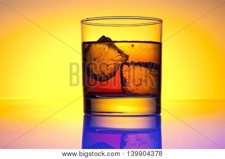 a glass with whiskey and yellow background