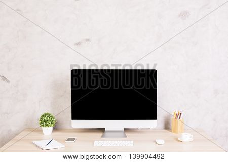 Front view of creative designer desktop with blank computer monitor coffee cup smartphone keyboard stationery items and plant on concrete wall background. Mock up