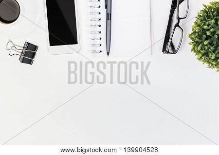 Top view and close up of white office desktop with spiral notepad other stationery items blank smartphone coffee cup and plant. Mock up