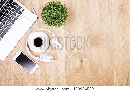 Top view of wooden office desktop with blank smartphone laptop keyboard coffee cup plant and headphones. Mock up