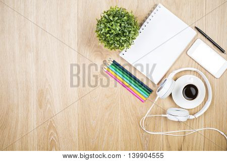 Top view of wooden desktop with blank spiral notepad coffee cup headphones blank white smartphone colorful pencils and decorative plant. Mock up