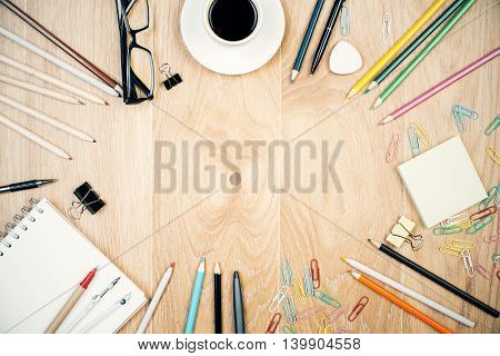 Wooden desktop with coffee cup and variety of colorful stationery items. Mock up