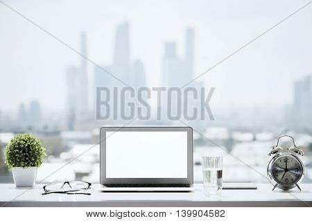 Closeup of blank white laptop on windowsill with a glass of water alarm clock glasses decorative plant and other items on blurry city background. Mock up