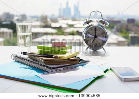 Pile of stationery items smartphone water glass and alarm clock on blurry city background