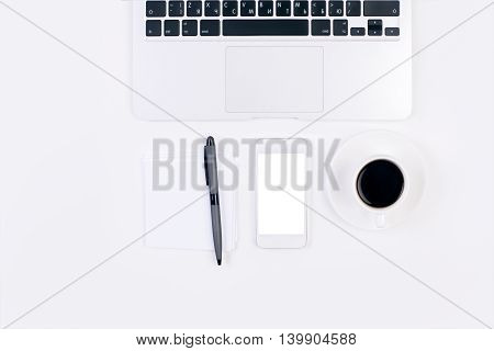 Top view of bright office desk with blank white cell phone coffee cup pen on a small piece of paper and laptop keyboard. Mock up