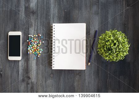 Blank spiral notepad mobile phone colorful pins pencil and plant in the middle of dark wooden desktop. Top view Close up Mock up