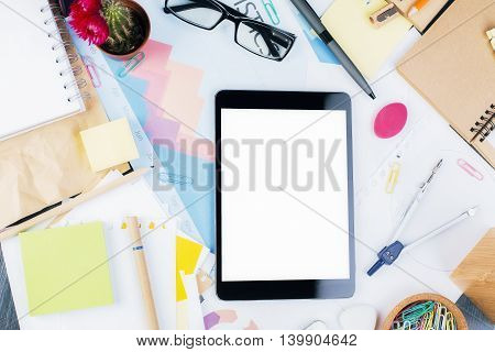 Blank white tablet on messy office desktop with business report cactus glasses and various stationery items. Top view Close up Mock up