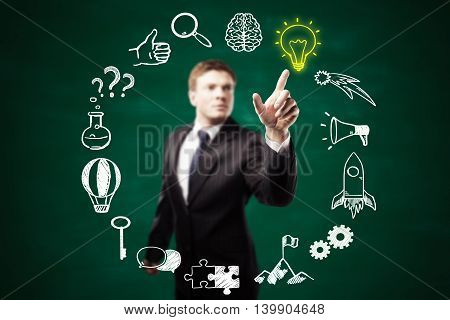 Blurry businessman pointing at round business icons sketch on chalkboard background. Success and idea concept