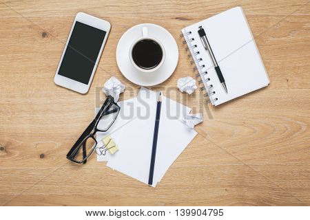 Top view of messy light wooden desktop with blank mobile phone glasses coffee cup spiral notepad pen and crumpled paper balls. Mock up