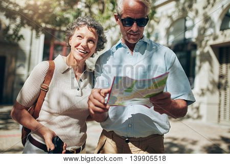 Mature Man And Woman Using  Map While Sightseeing.