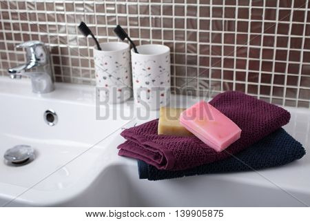 Soap, towels, toothbrushes and other accessories in a bathroom