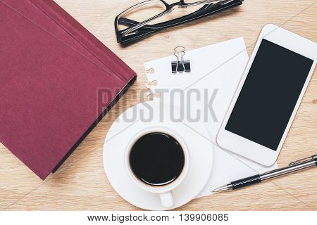 Top view of wooden office desktop with blank smartphone coffee cup closed red book glasses paper sheet peg and pen. Mock up