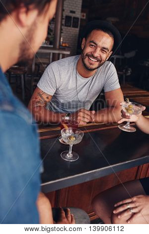 Happy young caucasian man sitting at a coffee shop with his friends. Young friends sitting at a cafe table having drinks.