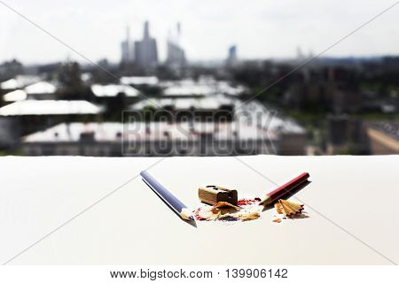 White surface with pencils sharpener and sawdust on blurry city background