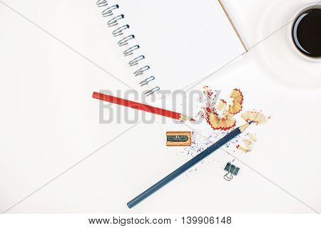 Top view and close up of white desktop with pencils sharpener sawdust small peg and eraser