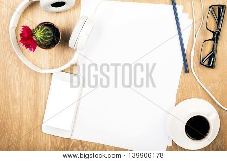 Top view of wooden desktop with blank paper sheets white smartphone coffee cup glasses headphones and small cactus in pot. Mock up