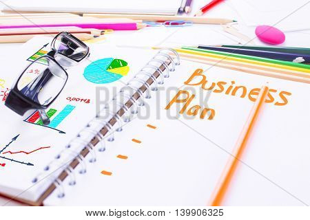 Closeup of spiral notepad with unfinished business plan and business charts surrounded with stationery items