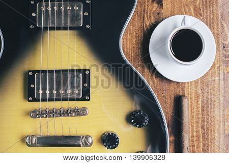 Top view and closeup of electric sunburst guitar coffee cup and cigar on wooden surface