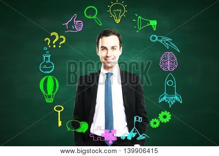 Confident smiling businessman with circular business sketch on chalkboard background. Success concept