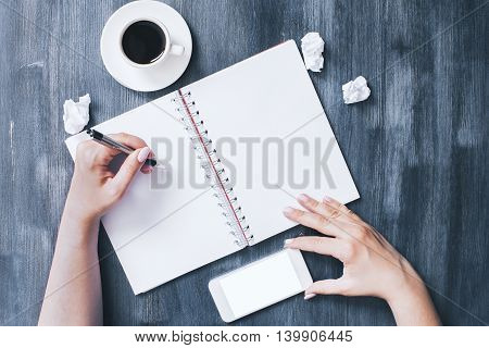 Female hands writing in spiral notepad and holding blank white smartphone on dark wooden desktop with coffee cup. Top view Mock up