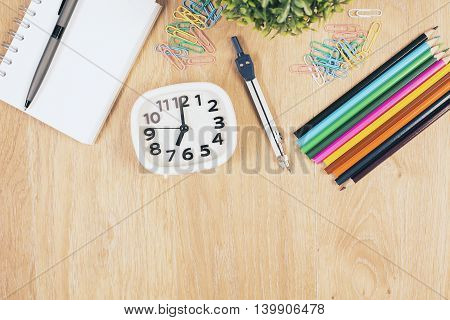 Top view of wooden desktop with colorful stationery items clock and plant. Mock up