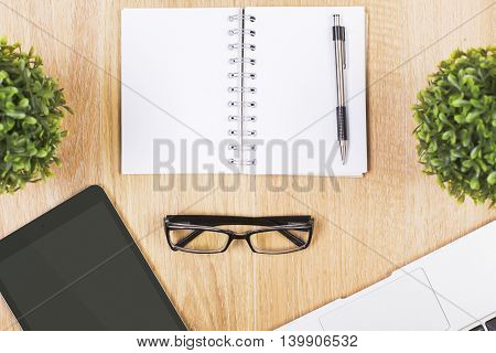Closeup of wooden desktop with blank spiral notepad pen glasses tablet decorative plants and keyboard. Mock up