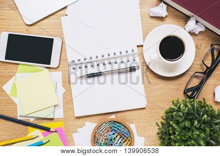 Messy workplace with blank smartphone open spiral notepad coffee cup glasses plant and various stationery items. Mock up