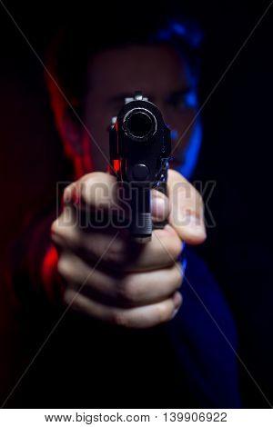 Officer or criminal holding a gun lit with police lights