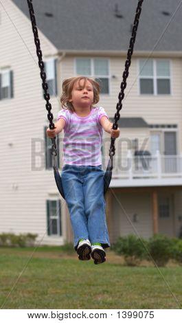 Kleines Mädchen auf Spielplatz-Schaukel