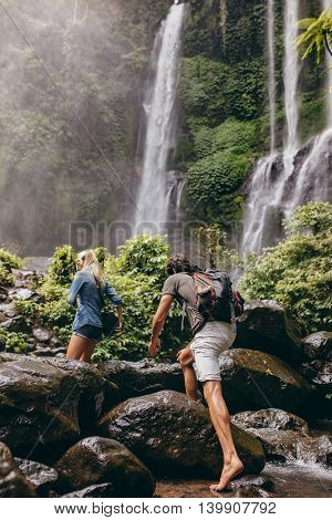 Couple Crossing A Stream Together In The Forest