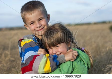 Two children brother and sister hugging each other