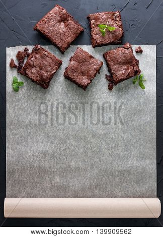few pieces of brownies on baking paper with space for information (top view). black concrete background. dark