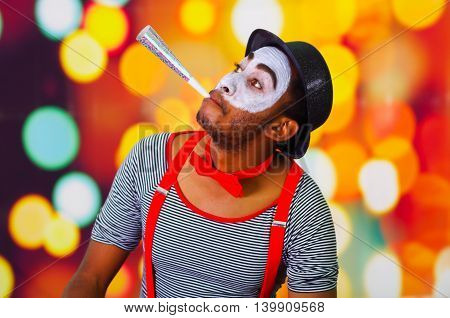 Headshot pantomime man with facial paint posing for camera using blow horn, blurry lights background.