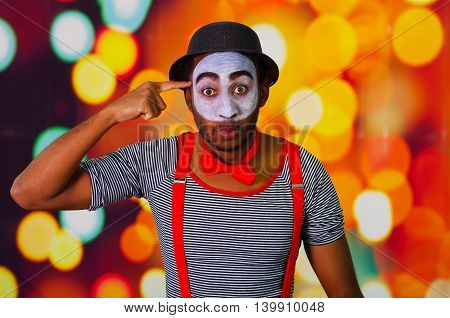 Pantomime man wearing facial paint posing for camera, using hands interacting body language, blurry lights background.