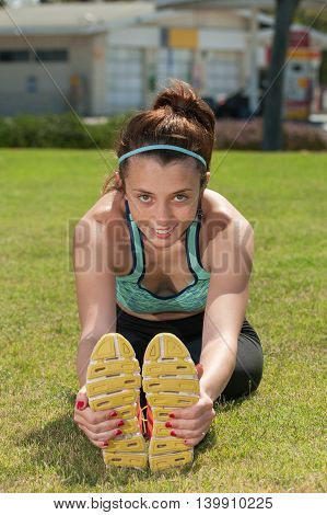 Female teenage runner stretching to grab her soles.