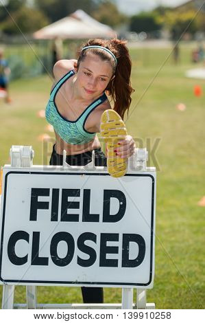 Muscular female teen stretching on closed sign.