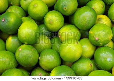 Greenish yellow limes piled for market detail