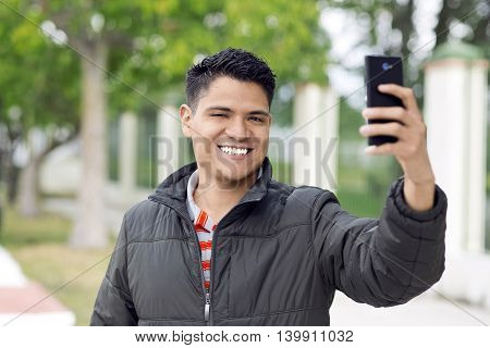 Latin young man smiling outdoors taking photos with a smartphone in the park