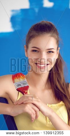 Happy beautiful young woman doing wall painting, standing near ladder