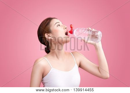 Cheerful beautiful sporty asian young woman holding a bottle of water on pink background.
