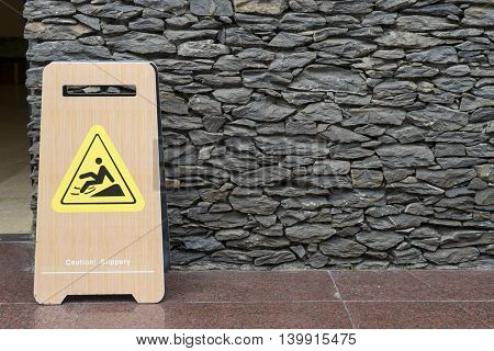 Warning sign for wet floor on the pathway