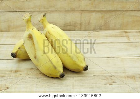 Cultivated Asian yellow banana on wood background. Thai name Klay Nam Wa.