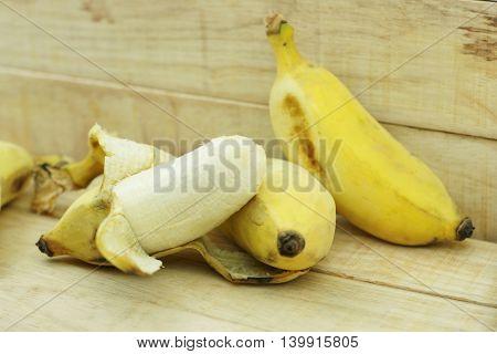 Half peeled Asian yellow banana on wood background. Thai name Klay Nam Wa.