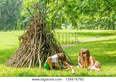 outdoor portrait of three happy kids - boy and girls - playing next to wooden stick hut house, looking like indian tepee, on natural background