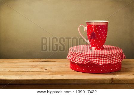 Tea cup with Christmas tree and gift box with polka dots on wooden table