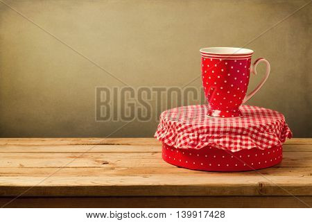 Coffee cup and gift box with polka dots pattern on wooden table