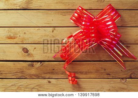 Wooden background with ribbon red bow for holiday decoration